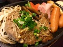 Καυτά χάμπουργκερ χοιρινού κρέατος και τηγάνι λουκάνικων Στοκ Φωτογραφία