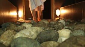 Καυτές πέτρες στη σάουνα και έναν κάδο των ποδιών των ατόμων κινηματογραφήσεων σε πρώτο πλάνο νερού φιλμ μικρού μήκους