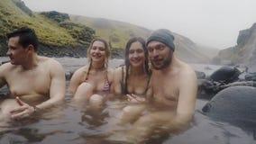 Καυτή γεωθερμική SPA άνοιξη στην Ισλανδία Διακινούμενη χαλάρωση ζευγών δύο στην καυτή λίμνη στην Ισλανδία Τουρίστες που απολαμβάν φιλμ μικρού μήκους