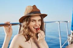 Καυτή ευρωπαϊκή πρότυπη φράουλα κατανάλωσης καθμένος στο γιοτ κάτω από τον ήλιο, που φορά το καπέλο αχύρου Διαφήμιση και διακοπές Στοκ φωτογραφίες με δικαίωμα ελεύθερης χρήσης