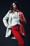 Καυτή θέτοντας γυναίκα στο κόκκινο παντελόνι και το άσπρο παλτό Στοκ Εικόνα