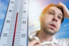 Καυτή καιρική έννοια Ο νεαρός άνδρας ιδρώνει Το θερμόμετρο παρουσιάζει υψηλής θερμοκρασίας Ήλιος στο υπόβαθρο Στοκ φωτογραφίες με δικαίωμα ελεύθερης χρήσης