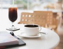Καυτή μαύρη κούπα καφέ στον πίνακα στον κενούς καφέ/το εστιατόριο Έννοια της μοναξιάς, απομόνωση, εγκατάλειψη ή απόμερος στοκ εικόνες