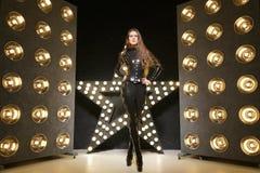 Καυτή μοντέρνη τοποθέτηση photomodel στο μοντέρνο catsuit λατέξ και τις υψηλές μπότες τακουνιών στοκ φωτογραφία με δικαίωμα ελεύθερης χρήσης