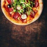 Καυτή πίτσα με το arugula, το σαλάμι, τις ελιές και το τυρί σε ένα αγροτικό W Στοκ Εικόνες