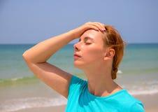 Καυτή παραλία και νέα γυναίκα Γυναίκα στην καυτή παραλία με την ηλίαση Πρόβλημα υγείας στις διακοπές Στοκ Φωτογραφία