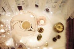Καυτή σοκολάτα, ένα φλυτζάνι του cappuccino σε μια καρέκλα γουνών Θερμό μαντίλι, κώνοι, φω'τα γύρω Άνετα χειμερινά βράδια στοκ φωτογραφία