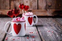 Καυτή σοκολάτα με ρόδινο marshmallow στις κούπες με τις καρδιές για την ημέρα βαλεντίνων στοκ φωτογραφία