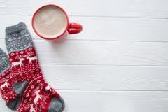 Καυτή σοκολάτα στο κόκκινο φλυτζάνι και κόκκινες κάλτσες με το traditiona Χριστουγέννων στοκ εικόνες