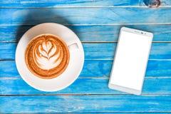 Καυτή σοκολάτα τοπ άποψης στο φλυτζάνι και smartphone με την κενή οθόνη ο Στοκ Φωτογραφίες
