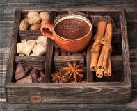 Καυτή σοκολάτα και εκλεκτής ποιότητας ξύλινο κιβώτιο με τα καρυκεύματα στοκ φωτογραφία