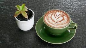 Καυτή τέχνη cappuccino καφέ latte στο φλυτζάνι χρώματος νεφριτών στο μαύρο επιτραπέζιο υπόβαθρο πετρών με τις εγκαταστάσεις κάκτω Στοκ φωτογραφία με δικαίωμα ελεύθερης χρήσης