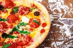 Καυτή φέτα πιτσών με Pepperoni, ντομάτες, λειώνοντας τυρί σε έναν αγροτικό ξύλινο πίνακα κοντά επάνω διάστημα αντιγράφων Στοκ εικόνα με δικαίωμα ελεύθερης χρήσης