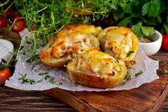 Καυτή ψημένη γεμισμένη πατάτα με το τυρί, μπέϊκον, μαϊντανός στον ξύλινο πίνακα Στοκ Φωτογραφία