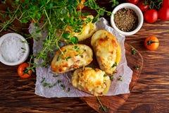 Καυτή ψημένη γεμισμένη πατάτα με το τυρί, μπέϊκον, μαϊντανός στον ξύλινο πίνακα Στοκ Εικόνα