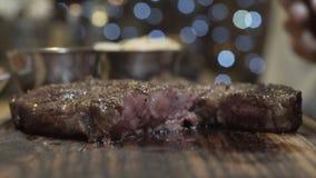Καυτή juicy μπριζόλα που κόβεται με το μαχαίρι σε έναν ξύλινο πίνακα κατά την άποψη κινηματογραφήσεων σε πρώτο πλάνο Μέσος σπάνιο στοκ φωτογραφίες
