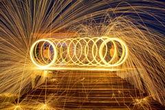 Καυτοί χρυσοί σπινθήρες που πετούν από το περιστρεφόμενο καίγοντας μαλλί χάλυβα ατόμων Στοκ Εικόνες
