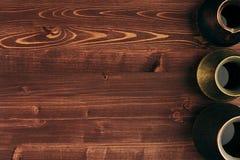 Καυτός καφές στα διαφορετικά καλά shabby τουρκικά δοχεία cezve με το διάστημα αντιγράφων στο καφετί παλαιό ξύλινο υπόβαθρο πινάκω στοκ εικόνες