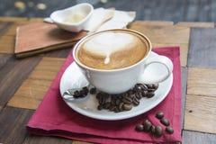 Καυτός καφές στο άσπρο φλυτζάνι στον ξύλινο πίνακα Στοκ Φωτογραφία