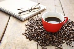 Καυτός καφές στο κόκκινο φλυτζάνι στον ξύλινο πίνακα Στοκ Φωτογραφία