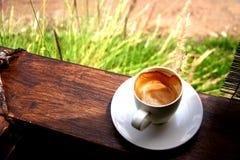 Καυτός καφές στο ξύλινο μπαλκόνι με το υπόβαθρο χλοών Στοκ Φωτογραφία