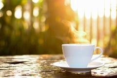 Καυτός καφές στο φλυτζάνι στον παλαιό ξύλινο πίνακα με το υπόβαθρο φύσης θαμπάδων στοκ φωτογραφίες