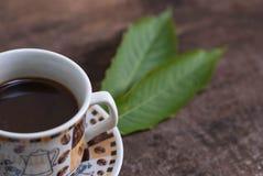 Καυτός καφές στο φλυτζάνι στον παλαιό ξύλινο πίνακα με το φύλλο στοκ εικόνα