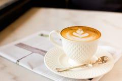 καυτός καφές τέχνης latte με την εφημερίδα στον ξύλινο πίνακα, τρύγος και Στοκ Φωτογραφίες
