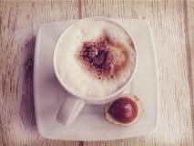 Καυτός καφές φθινοπώρου με τον αφρό και κάστανα σε ένα ξύλινο backgroun Στοκ Φωτογραφία