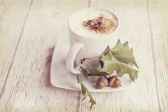Καυτός καφές φθινοπώρου με τον αφρό και κάστανα σε ένα ξύλινο backgroun Στοκ Εικόνες