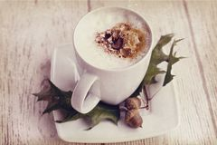 Καυτός καφές φθινοπώρου με τον αφρό και κάστανα σε ένα ξύλινο backgroun Στοκ Εικόνα