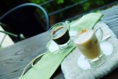 Καυτός καφές Cappuccino και καυτός καφές Americano στον ξύλινο πίνακα με την άνετη καφετερία Στοκ εικόνες με δικαίωμα ελεύθερης χρήσης
