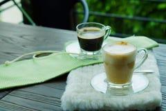 Καυτός καφές Cappuccino και καυτός καφές Americano στον ξύλινο πίνακα με την άνετη καφετερία Στοκ Φωτογραφία