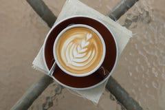Καυτός καφές latte με την όμορφη τέχνη αφρού στον πίνακα γυαλιού υπαίθριος Στοκ Εικόνα