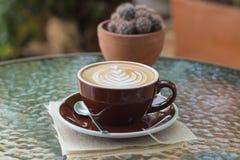 Καυτός καφές latte με την όμορφη τέχνη αφρού στον πίνακα γυαλιού υπαίθριος Στοκ εικόνες με δικαίωμα ελεύθερης χρήσης