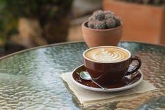Καυτός καφές latte με την όμορφη τέχνη αφρού στον πίνακα γυαλιού υπαίθριος Στοκ Φωτογραφίες