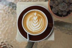 Καυτός καφές latte με την όμορφη τέχνη αφρού στον πίνακα γυαλιού υπαίθριος Στοκ φωτογραφίες με δικαίωμα ελεύθερης χρήσης