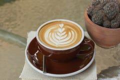 Καυτός καφές latte με την όμορφη τέχνη αφρού στον πίνακα γυαλιού υπαίθριος Στοκ Εικόνες