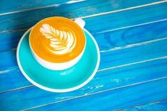 Καυτός καφές latte στο φλυτζάνι στον μπλε ξύλινο πίνακα Στοκ Εικόνες