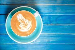 Καυτός καφές latte στο φλυτζάνι στον μπλε ξύλινο πίνακα Στοκ εικόνα με δικαίωμα ελεύθερης χρήσης