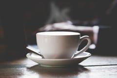 Καυτός μαύρος καφές σε έναν σκοτεινό τόνο ύφους φυσικού υποβάθρου θολωμένο στοκ εικόνες