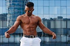 Καυτός όμορφος μαύρος τύπος με τους διογκώνοντας μυς που θέτουν ενάντια στο σκηνικό του αστικού τοπίου Πρότυπο ικανότητας ατόμων Στοκ Εικόνες