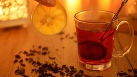 Καυτό αρωματικό τσάι σε ένα φλυτζάνι με ένα χέρι που κρατά ένα λεμόνι περιτύλιξη φιλμ μικρού μήκους