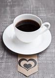 Καυτό λευκό φλυτζανιών καφέ στον ξύλινο πίνακα με την ετικέτα καρδιών Στοκ εικόνες με δικαίωμα ελεύθερης χρήσης