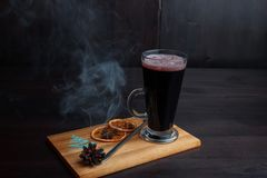 Καυτό εύγευστο πικάντικο θερμαμένο κόκκινο κρασί που διακοσμούνται με τις ξηρές πορτοκαλιές φέτες και μια σιγοκαίγοντας πρόσκρουσ στοκ φωτογραφία με δικαίωμα ελεύθερης χρήσης