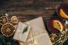 Καυτό θερμαμένο κρασί με τα καρυκεύματα και κιβώτιο δώρων στον ξύλινο πίνακα κορυφή VI Στοκ εικόνα με δικαίωμα ελεύθερης χρήσης