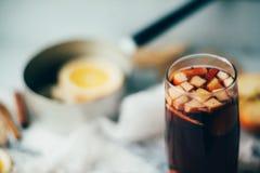 Καυτό θερμαμένο κρασί σε ένα γυαλί με τις πορτοκαλιά φέτες, το γλυκάνισο και τα ραβδιά κανέλας, μπισκότα αστεριών στον εκλεκτής π Στοκ Εικόνα