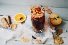 Καυτό θερμαμένο κρασί σε ένα γυαλί με τις πορτοκαλιά φέτες, το γλυκάνισο και τα ραβδιά κανέλας, μπισκότα αστεριών στον εκλεκτής π Στοκ Φωτογραφία