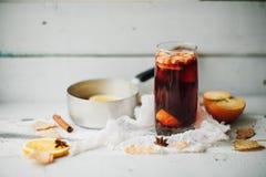 Καυτό θερμαμένο κρασί σε ένα γυαλί με τις πορτοκαλιά φέτες, το γλυκάνισο και τα ραβδιά κανέλας, μπισκότα αστεριών στον εκλεκτής π Στοκ φωτογραφία με δικαίωμα ελεύθερης χρήσης