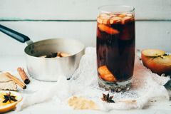 Καυτό θερμαμένο κρασί σε ένα γυαλί με τις πορτοκαλιά φέτες, το γλυκάνισο και τα ραβδιά κανέλας, μπισκότα αστεριών στον εκλεκτής π Στοκ εικόνα με δικαίωμα ελεύθερης χρήσης